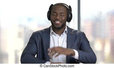 Black manager in headphones is dancing.