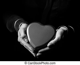woman hands isolated on black showing heart shaped candy box...