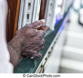 black mans hand on a railing of a streetcar in New Orleans