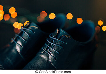Black man's shoes with laces. Against background bokeh.