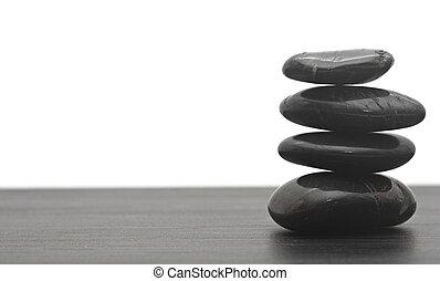 Black massage stones stacked, isolated.