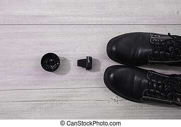 black men's shoes on the wooden background with untied laces, shoe polish