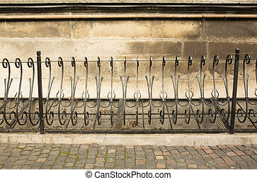 Black metal fence near the old wall in Lviv