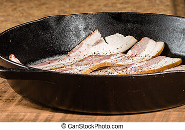 Black metal skillet or pan with bacon