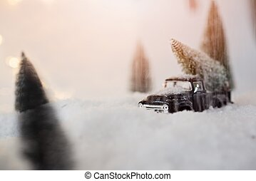 Black miniature car carrying Christmas tree.