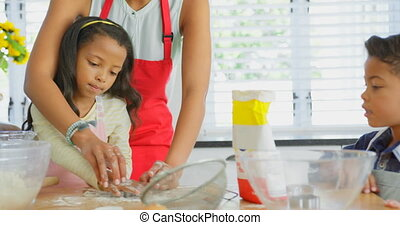 Black mother and daughter using cookie cutter in kitchen. Black mother helping her daughter in preparing food 4k