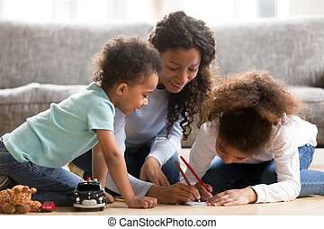 Black mother drawing with kids at home