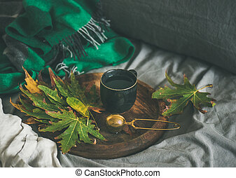 Fall morning tea in bed. Black mug of tea with sieve and fallen leaves on wooden tray over bed linen and blanket background, selective focus. Autumn mood concept