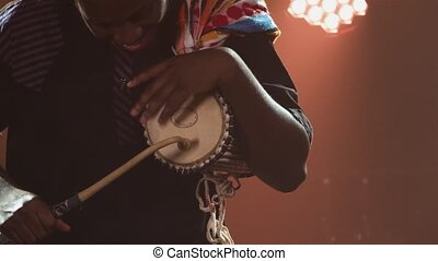 Black musician plays talking African yuka drum in a dark studio against a backdrop of bright lights and smoke. An African American man hits the drum and enjoys the music. African National Folklore. Close up