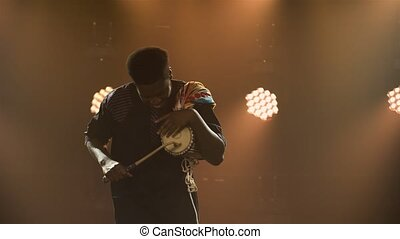Black musician plays talking African yuka drum in a dark studio against a backdrop of bright lights and smoke. An African American man hits the drum and enjoys the music. African National Folklore