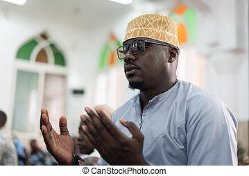 Black Muslim adult man praying inside mosque on Friday prayer