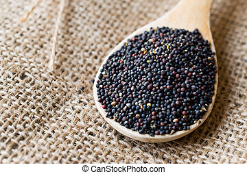 Black Mustard Seeds in Wooden Spoon with Sack