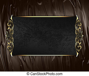 Black name plate with gold ornate edges, on brown background