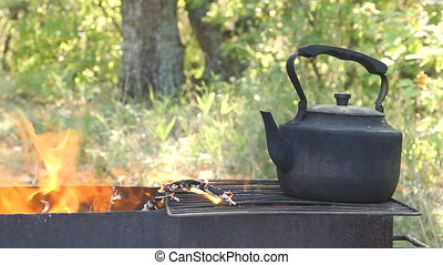 Black old smoked teapot on the campfire at sunny day