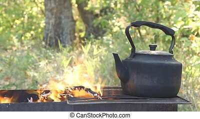 Black old smoked teapot on the camp