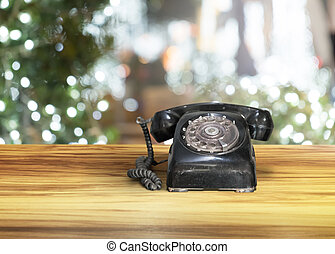 black old vintage telephone on wooden brown table with night bokeh background