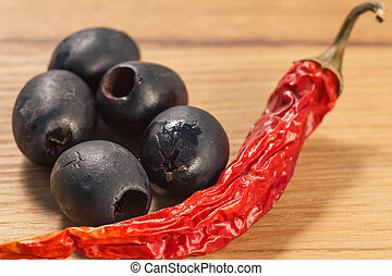 Black olives and dried red pepper on cutting board