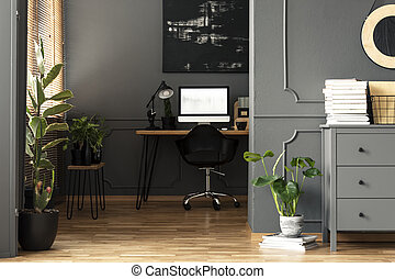 Black painting above desk with lamp and computer desktop in grey apartment interior. Real photo
