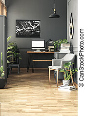 Black painting above desk with mockup of computer desktop in grey freelancer's interior. Real photo