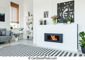 Black painting above fireplace in white living room interior...