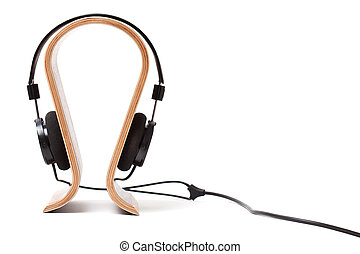 Black Pair of Headphones on a wooden stand. Isolated