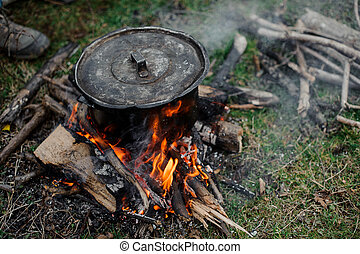 Black pan with a cover standing on the bonfire in the forest