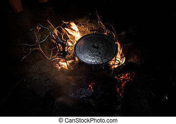 Black pan with a cover standing on the bonfire in the night