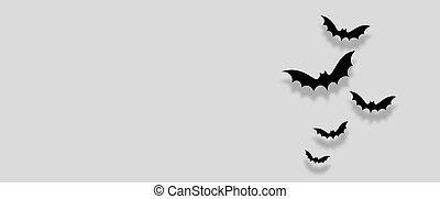 Black paper bats flying over white background. Halloween concept. Flat lay