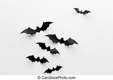 black paper bats over white background - halloween and...