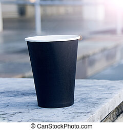 Black paper cup of coffee on stairs background