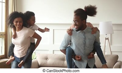 Black parents give piggyback ride carrying children playing at home