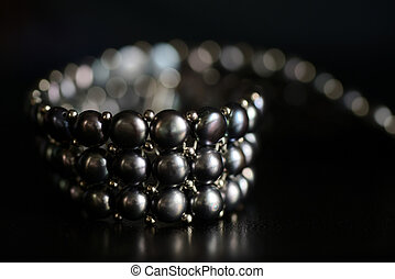 Black pearl necklace on a dark background close up