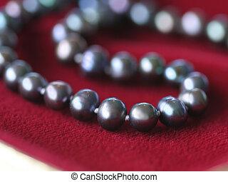 Black pearl necklace on red velvet