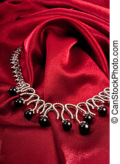 Black pearls on red textile