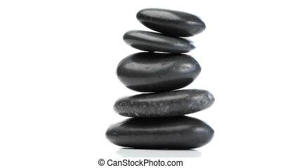 Black pebbles rotating - Pile of Black pebbles rotating on a...