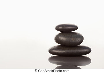 Black pebbles stack on a mirror