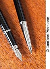 black pen on wooden desk