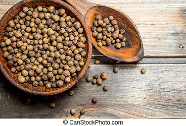 Black pepper in a bowl and spoon.