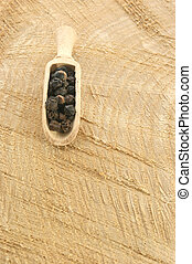 black pepper in a wooden shovel on a timber board