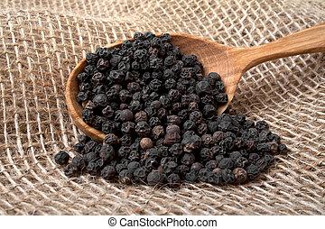 Black pepper in wooden spoon on burlap background
