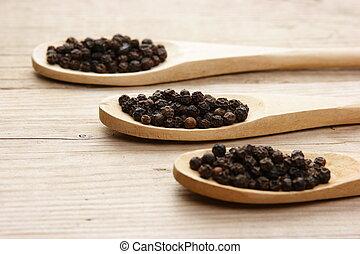 Black pepper in wooden spoon on the old board