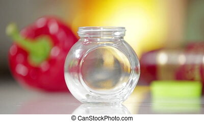 Black peppercorns falling in glass jar. Music Kitchen