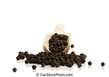 black peppercorns skidding from a small wooden shovel front on white background