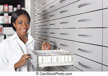 Black pharmacist at medicine cabinet