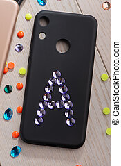 Black phone case decorated with A letter. Rhinestone art
