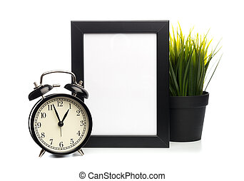 black photo frame and clock isolated on white background, plant behind.