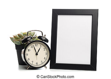 black photo frame and clock isolated on white background, succulent behind.