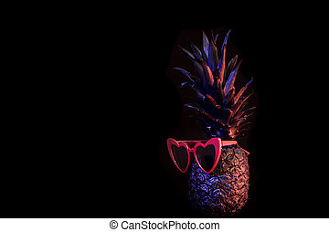 Black pineapple with glasses on black background