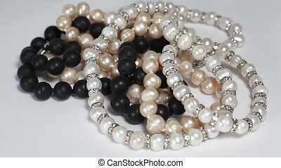 Black, pink and white  pearls necklaces turning close up