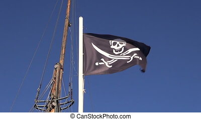 Black pirate flag waving in the wind on the ship - Pirate...